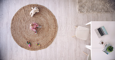 Buy stock photo High angle shot of an adorable baby sitting on the floor while playing with toys at home