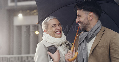 Buy stock photo Cropped shot of an affectionate young couple standing under an umbrella together while in the city