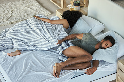 Buy stock photo Shot of a woman sleeping with a duvet wrapped around her while her husband lays uncovered