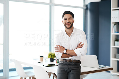 Buy stock photo Cropped portrait of a handsome young businessman sitting with his arms folded in his office alone