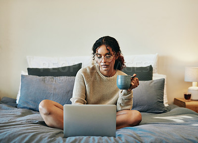 Buy stock photo Shot of an attractive young woman using her laptop while relaxing on her bed