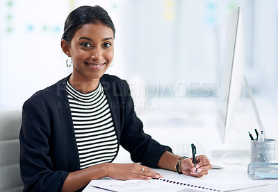 Buy stock photo Portrait of an attractive young businesswoman going over paperwork inside her office at work