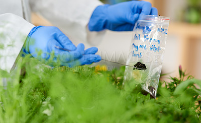 Buy stock photo Closeup shot of an unrecognisable scientist putting soil samples into a bag in a lab