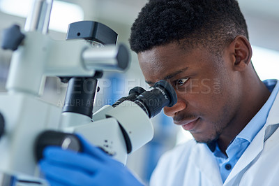 Buy stock photo Cropped shot of a focused young male scientist looking at test samples through a microscope inside of a laboratory during the day