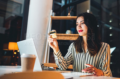 Buy stock photo Shot of a young businesswoman using a credit card and digital tablet during a late night at work