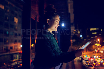 Buy stock photo Cropped shot of an attractive young businesswoman smiling while using a digital tablet on a balcony at night