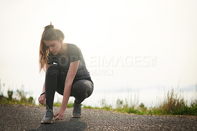 Buy stock photo Shot of a sporty young woman tying her shoelaces while exercising outdoors