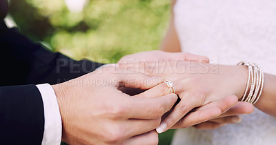 Buy stock photo Cropped shot of an unrecognizable groom slipping a ring onto his bride's finger on their wedding day