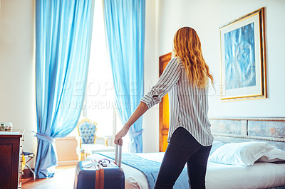 Buy stock photo Rearview shot of a young businesswoman standing with her suitcase inside a hotel room