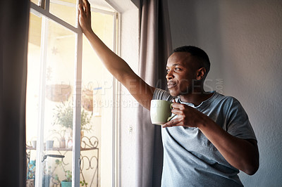 Buy stock photo Cropped shot of a handsome young man standing and looking contemplative in his bedroom while enjoying a cup of coffee