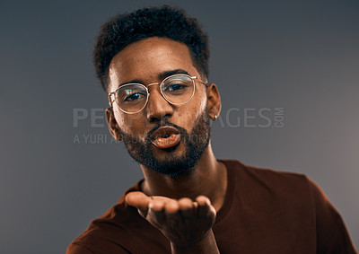 Buy stock photo Studio portrait a handsome young man blowing a kiss while standing against a grey background
