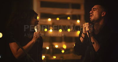 Buy stock photo Shot of a young man and woman singing on stage in a club