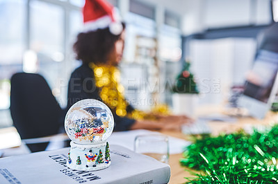 Buy stock photo Cropped shot of a snow globe sitting on a stack of books while an unrecognizable businesswoman works in the background
