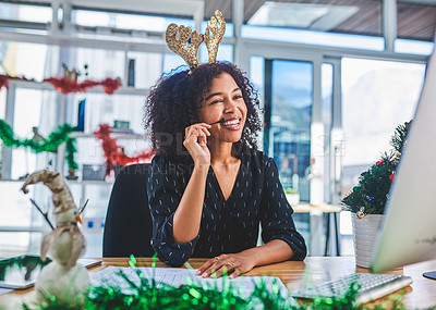 Buy stock photo Cropped shot of an attractive young customer service agent sitting alone in the office and wearing christmas decorations