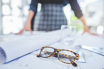 Buy stock photo Closeup shot of a pair of spectacles and blueprints on a table with an unrecognisable businesswoman in the background