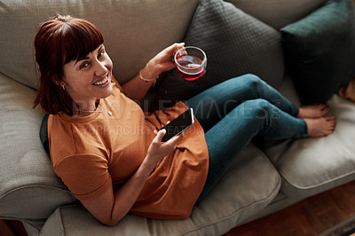 Buy stock photo Shot of a woman having a cup of tea while using her cellphone at home