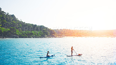 Buy stock photo Shot of a man and woman paddle boarding across the sea.