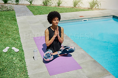 Buy stock photo Shot of a young woman meditating in her backyard