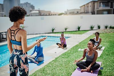 Buy stock photo Shot of a young woman giving a yoga class in a garden