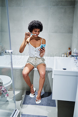 Buy stock photo Shot of a carefree young woman texting on her cellphone while rushing her teeth inside of a bathroom in the morning