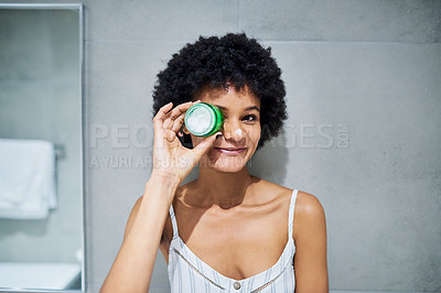 Buy stock photo Portrait of a cheerful young woman holding a tub of skin moisturizer to apply it on her face inside of a bathroom during the morning hours