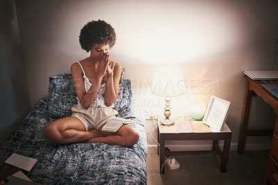 Buy stock photo Full length shot of an attractive young woman sitting on her bed at home and praying after reading her bible