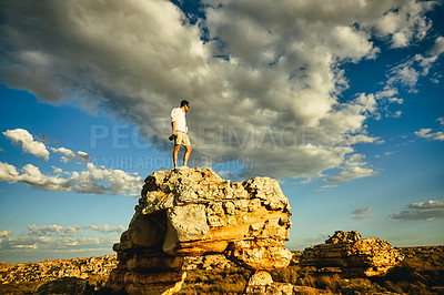 Buy stock photo Shot of a young man holding a camera while standing on a cliff in a rural landscape