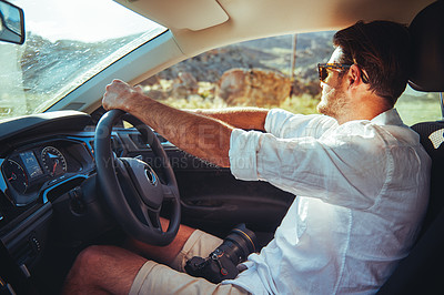 Buy stock photo Shot of a young man driving a car in a rural area
