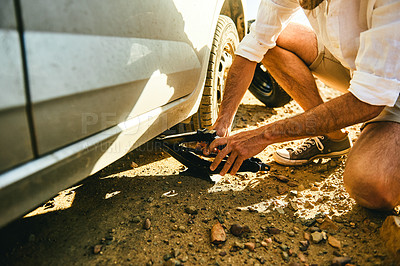 Buy stock photo Closeup shot of a man changing a flat tyre on his car in a rural area