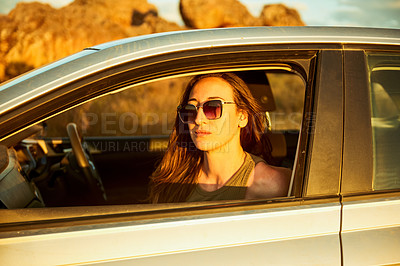 Buy stock photo Portrait of a young woman looking out the window in a car while on a road trip
