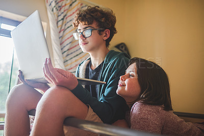 Buy stock photo Shot of a teenage boy and his younger sister watching something on a laptop