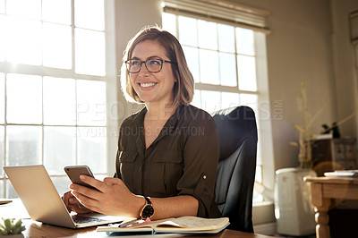 Buy stock photo Cropped shot of a businesswoman using a laptop and cellphone at her desk