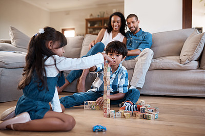 Buy stock photo Shot of two young siblings playing with their toys while their parents sit and watch in the background