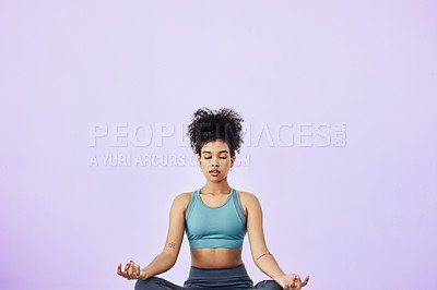 Buy stock photo Studio shot of a fit young woman meditating against a purple background