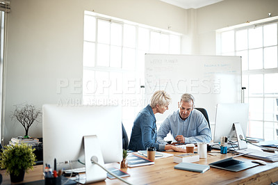 Buy stock photo Cropped shot of two business colleagues sitting together and going through paperwork in the office