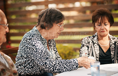 Buy stock photo Cropped shot of a senior woman sitting and talking with her friends during a tea party outdoors