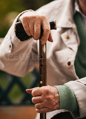 Buy stock photo Cropped shot of an unrecognizable senior woman sitting outdoors alone and holding her walking stick