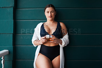 Buy stock photo Cropped portrait of an attractive young woman holding a glass of tea while standing outdoors in the morning at home