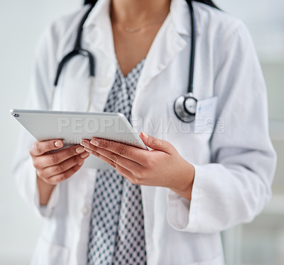 Buy stock photo Cropped shot of an unrecognizable doctor using a digital tablet while working in a clinic