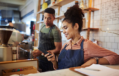 Buy stock photo Shot of a young woman using a phone while working in a cafe