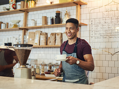 Buy stock photo Shot of a young waiter holding a cup of coffee in a cafe