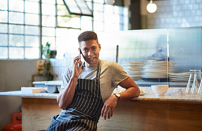Buy stock photo Portrait of a young man talking on a cellphone while working in a cafe