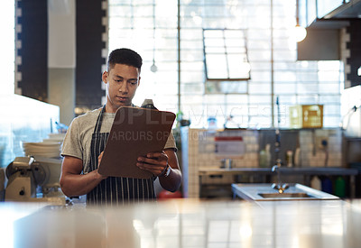 Buy stock photo Shot of a young man using a clipboard while working in a cafe