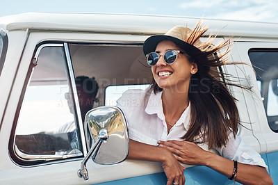 Buy stock photo Shot of a happy young woman enjoying a road trip