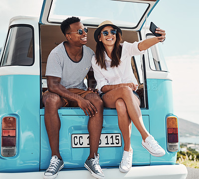 Buy stock photo Shot of a young couple taking a selfie while out on a road trip