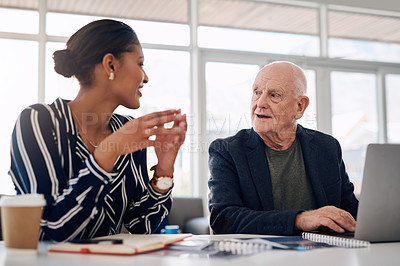 Buy stock photo Cropped shot of two businesspeople having a discussion while working together in a modern office