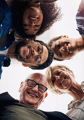 Buy stock photo Low angle portrait of a diverse group of businesspeople standing in a huddle in a modern office