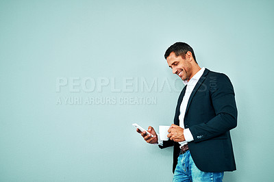 Buy stock photo Studio shot of a mature businessman using a smartphone against a blue background