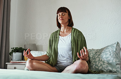 Buy stock photo Full length shot of an attractive young woman meditating while sitting on her bed at home