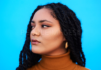 Buy stock photo Cropped shot of a beautiful young woman posing against a blue wall